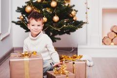 En gullig pojke som squatting bredvid en julgran, bredvid många gåvor med guld- band och pilbågar Grabb i en stucken tröja och va Arkivbild