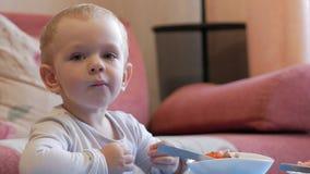 En gullig pys äter havregröt med stycken av kött på en tabell för barn` s Hem- inredningar arkivfilmer