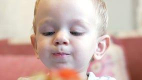 En gullig pys äter havregröt med stycken av kött på en tabell för barn` s Hem- inredningar stock video