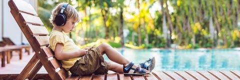 En gullig pys använder en smartphone och hörlurar som ligger på en deckchair vid pölen primär utbildning, kamratskap, barndom, royaltyfria bilder