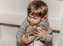 En gullig pys med en skurk- framsida har hans lilla skor i hans händer royaltyfri fotografi