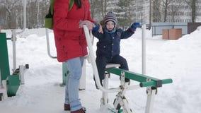 En gullig pys och en ung moder är förlovade i utomhus- övningsutrustning Det ` s hårt för att en unge ska nå handtagen lager videofilmer