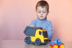 En gullig pys som spelar med samlingen för modellbil Leksakröra i barnrum royaltyfri fotografi