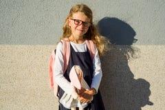 En gullig skolflicka av grundskola för barn mellan 5 och 11 år är att le som rymmer en leksak Arkivfoto