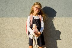 En gullig skolflicka av grundskola för barn mellan 5 och 11 år ler med en leksak i henne Royaltyfri Fotografi