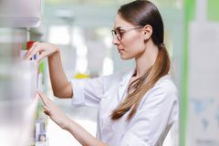 En gullig tunn dam med mörkt hår och exponeringsglas som bär ett labblag, tar något från hyllan i ett aktuellt apotek fotografering för bildbyråer