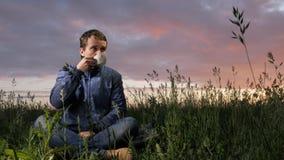 En gullig ung man dricker en varm drink på solnedgången på fältet Härlig himmel på en bakgrund stock video