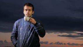 En gullig ung man dricker en varm drink på solnedgången på fältet Härlig himmel på en bakgrund arkivfilmer