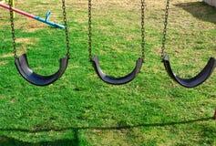 En gunga som göras av gummihjul på gräsmattan lekplats royaltyfria bilder