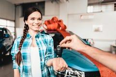 En Guy Gives en biltangent till flickvännen begreppsgåva som isoleras över white royaltyfria foton