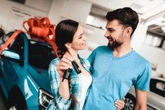 En Guy Gives en biltangent till flickvännen begreppsgåva som isoleras över white fotografering för bildbyråer