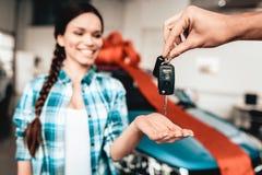 En Guy Gives en biltangent till flickvännen begreppsgåva som isoleras över white royaltyfri bild