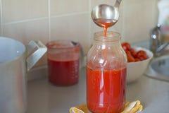 En häller tomatfruktsaft i gruppen arkivbilder