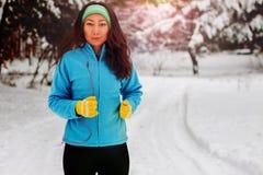 En härlig asiatisk kvinna i en träningsoverall kör med ett leende i parkerar i vinter arkivfoto