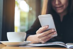 En härlig asiatisk kvinna med innehavet och att använda för smileyframsida den smarta telefonen medan läs- tidskrifter med kaffek arkivbild