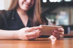 En härlig asiatisk kvinna med smileyframsidan som rymmer och använder som är horisontal, ilar telefonen till hållande ögonen på t arkivfoto