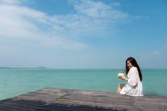 En härlig asiatisk kvinna på vitt klänningsammanträde på terrassen som dricker kokosnötfruktsaft med bakgrund för hav och för blå fotografering för bildbyråer