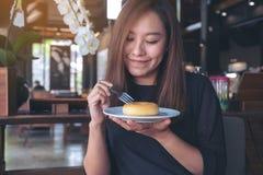 En härlig asiatisk kvinna som rymmer ett stycke av munken och gaffeln med mening lyckligt arkivbild