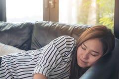 En härlig asiatisk kvinna som tar en ta sig en tupplur under dag med kopplad av känsla royaltyfria bilder