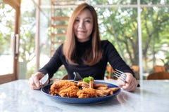 En härlig asiatisk kvinna tycker om att äta stekt kyckling, och fransmannen steker i restaurang royaltyfri foto