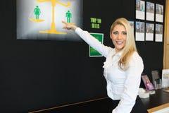 En härlig blond affärskvinna som pekar en bild Arkivfoto