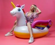 En härlig blond flicka i sexiga sundress med slanka ben i vita gymnastikskor sitter på en uppblåsbar mång--färgad enhörning royaltyfria bilder