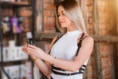 En härlig blond kvinna annonserar skönhetsmedel, rymmer ett svart rör på hennes hand Håromsorg, hud, royaltyfria bilder