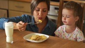 En härlig brunett matar hennes dotter Hon blåser på mat och ger den till flickan Behandla som ett barn mat, sund aptit A lager videofilmer