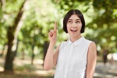 En härlig brunettaffärskvinna som pekar upp och ler Lycklig flicka som bär en vit blus på en naturlig grön bakgrund Royaltyfria Bilder