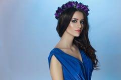 En härlig brunettmodell med utgör och lockigt långt hår och kronan med violetsblommor på hennes huvud royaltyfri fotografi