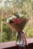 en härlig bukett av rosa och vita blommor på en skogbakgrund Arkivbilder