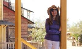 En härlig cowgirl i en gammal västra stad Royaltyfria Bilder