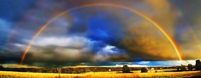En härlig dubbel regnbåge över det guld- fältet fotografering för bildbyråer