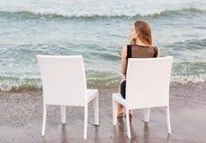 En härlig ensam flicka i en svart klänning och med långt blont hår sitter på en stol och ser havet Arkivbild