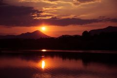 En härlig färgrik solnedgång över bergen, sjö och skog i purpurfärgade signaler Abstrakt begrepp ljust landskap royaltyfri fotografi