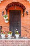 En härlig farstubro i ett rikt hus med den svarta dörren, wal röd tegelsten royaltyfri bild