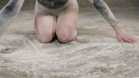 En härlig flicka förorenas med vitt pulver eller mjöl som sitter på golvet i en svart dräkt och gör konstcirklar stock video
