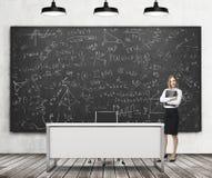 En härlig flicka framlägger matematikberäkningar på det svarta kritabrädet i ett modernt klassrum Tre svarta takljus, träflo Fotografering för Bildbyråer