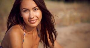 En härlig flicka i en bikini häller sanden Arkivfoton