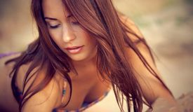 En härlig flicka i en bikini häller sanden Royaltyfri Foto