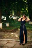 En härlig flicka i en blå klänning går i parkera Royaltyfri Fotografi