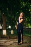 En härlig flicka i en blå klänning går i parkera Royaltyfri Bild