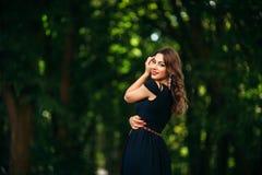 En härlig flicka i en blå klänning går i parkera Royaltyfri Foto