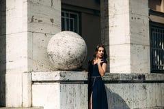 En härlig flicka i en blå klänning går i parkera Arkivfoton