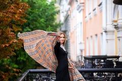 En härlig flicka i ett ljust mång--färgat lag i regnigt väder arkivfoto