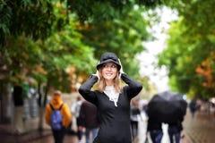 En härlig flicka i ett ljust mång--färgat lag i regnigt väder royaltyfri bild