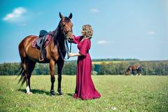 En härlig flicka i en lång burgundy klänning arkivfoton