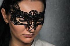 En härlig flicka i en openwork karnevalmaskering med chic snärtar royaltyfri bild