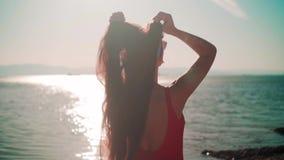 En härlig flicka i en röd baddräkt i ett stycke och exponeringsglasställningar på kusten Flickan trycker på hennes hår arkivfilmer