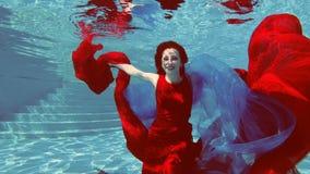 En härlig flicka i en röd klänning med rött hår simmar och poserar undervattens- i en utomhus- pöl med en röd och blå torkduk i h